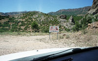 Gravel road with warning signs through the Taurus Mountains, Turkey
