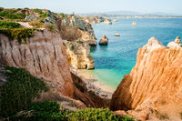Camilo Beach in Lagos, Algarve, Portugal. A tiny secret beach between the limestone walls. 200 wooden steps down to sheltered, sandy cove divided by ochre-colored rocks with hand-dug tunnel.
