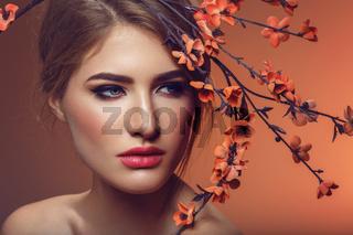 Beautiful girl with sakura branch