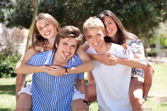 group of happy young men's piggybacking thier girlfriends