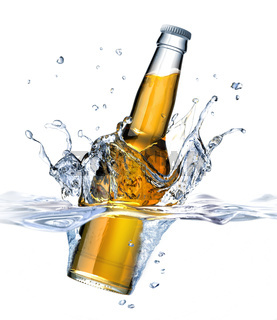 Clear Beer bottle falling into water, forming a crown splash. Viewed from a side close up.