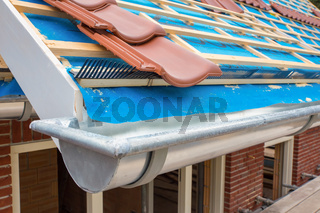 Zinc gutter and tiles on roof pitch of house