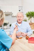 Alter Mann spielt mit Altenpflegerin