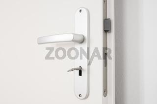 metallic door handle with key on white door