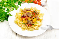 Farfalle with turkey and vegetables in plate on board
