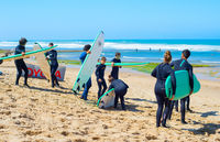 Group of surfers beach surfing