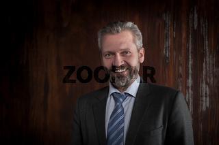 Portrait of a mature smiling businessman on black background