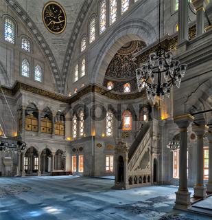 Interior shot of Nuruosmaniye Mosque with minbar (platform), huge arches  colored stained glass windows, Istanbul, Turkey