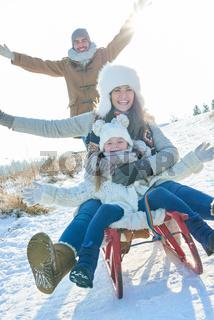 Familie hat Spaß beim Schlitten fahren