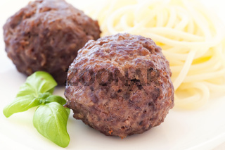 Roasted meatballs with spaghetti as closeup on a white plate