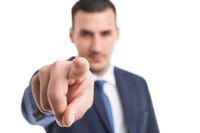 Focus on businessman index finger pointing at camera