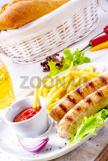 grilled bratwurst with chips and cold beer