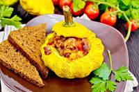 Squash yellow stuffed with meat and vegetables on board