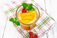 Lemonade with cherry and orange in wineglass on light board