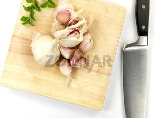 Garlic on a cutting board isolated against a white background