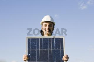 Hübsche Frau hält einen Solarmodul vor einem