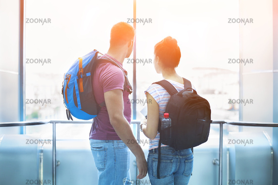 Traveler couple in love with backpacks indoors