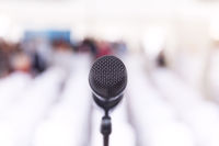 Microphone in focus, conference hall without auditorium in the background