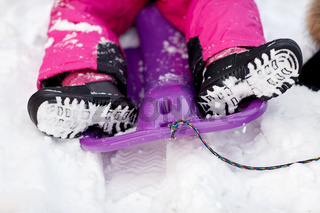close up of kids feet in winter boots on sled