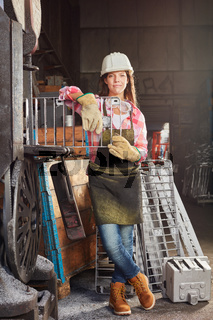Frau in Arbeitskleidung mit Gussform