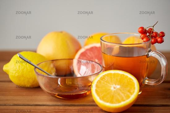 tea with honey, lemon and rowanberry on wood