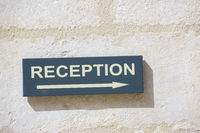 sign attached to a white wall indicating where the reception area is.