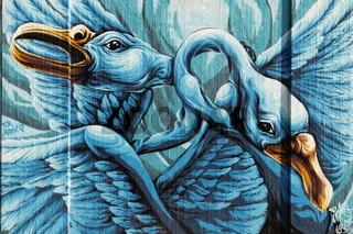 Wall with graffiti - two blue bird heads.