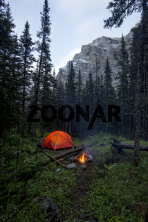 Tent and campfire wild camping in a forest with mountains