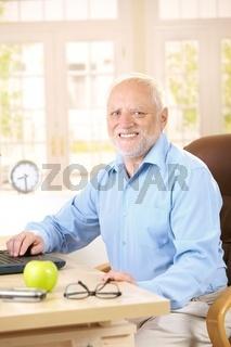 Portrait of senior man at desk