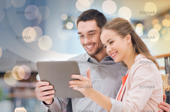 happy couple with tablet pc taking selfie in mall
