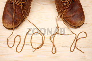 Pair of work shoes with shoelaces on wooden background