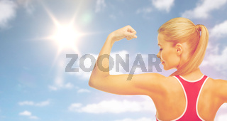 happy sporty woman showing biceps over sky and sun