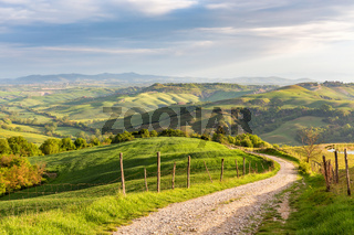 Rural view of the valley with a rolling landscape and a dirt road in Tuscany, Italy