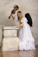 Young blond woman in wedding dress with black wings and a violin