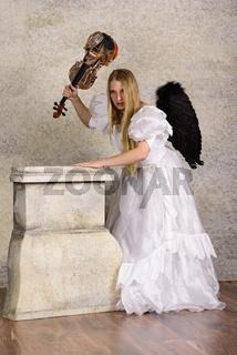 Junge blonde Frau im Brautkleid mit schwarzen Flügeln und einer Geige