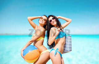 happy young women in bikini posing on summer beach