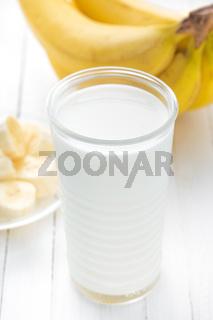 Yogurt with fresh bananas on white wooden background closeup, healthy breakfast