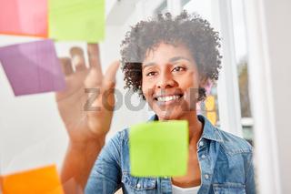 Business Frau im Ideen Workshop liest Haftnotizen