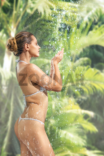 Woman enjoying shower in tropical SPA