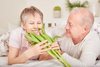 Ältere Frau bekommt Blumen geschenkt