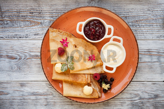 Pancakes with cream and jam and fresh berries on a plate