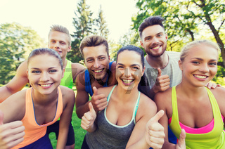 group of happy sporty friends showing thumbs up