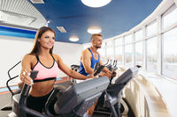 Young couple exercising on bikes in fitness gym