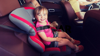 happy child sitting in car seat and father driving