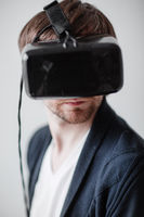 selective focus on face. Handsome man wearing virtual reality glasses isolated  a gray background
