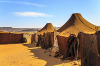 Tents in the middle of desert with mountains in the background, on a sunny day