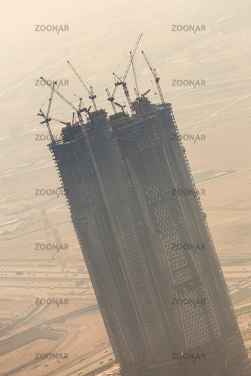 Skyscrappers construction site with cranes on top of buildings.