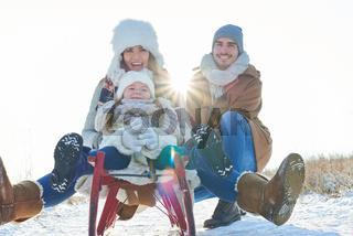 Familie mit Kind beim Schlitten fahren