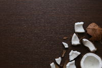 the halved coconut on dark wooden background
