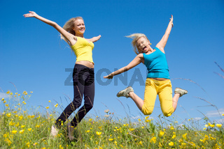 woman jumping on background meadow and blue sky
